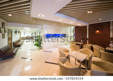 Beautiful large reception of business company with tables, chairs and aquarium. - stock photo