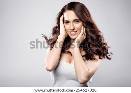 Beautiful latin brunette woman with long shiny brown hair and clean skin. Portrait of a fashion model in studio - stock photo
