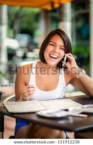 Beautiful latin girl in a restaurant outdoors talking on mobile phone - stock photo