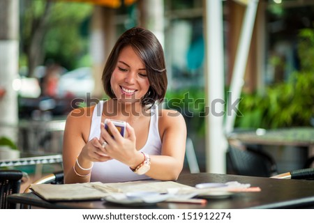 Beautiful latin girl texting on mobile phone - stock photo