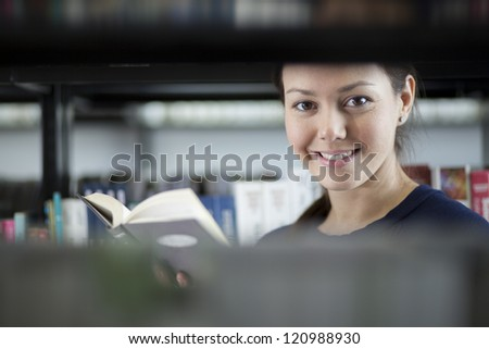 Beautiful latin student spending some time at the library - stock photo