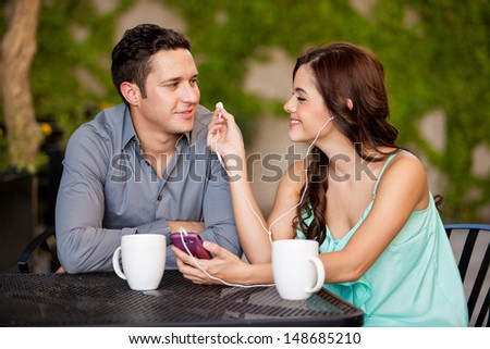 Beautiful Latin woman and her boyfriend listening to music together on a date