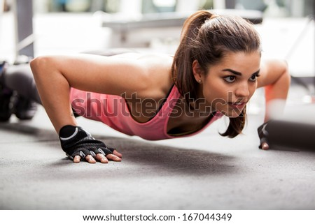 Beautiful Latin woman doing push ups in the gym before lifting some weights