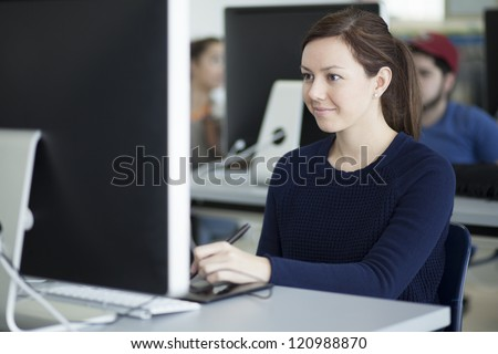 Beautiful latin woman doing some design work with a tablet - stock photo