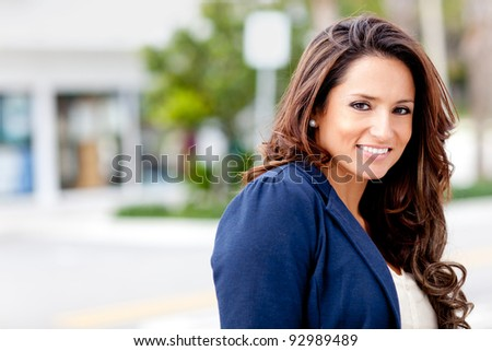 Beautiful Latin woman looking happy and smiling - stock photo