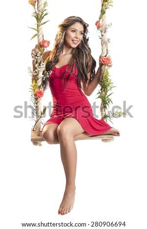 Beautiful latin woman on swing on white background - stock photo