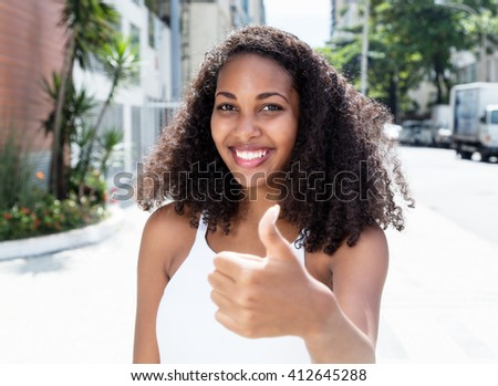 Beautiful latin woman with curly hair in city showing thumb - stock photo