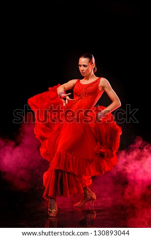 Beautiful Latino dancer in action. Over dark smoky background