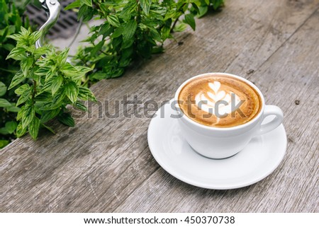 Beautiful Latte art coffee cup on wood table with green leave frame, Coffee art   - stock photo
