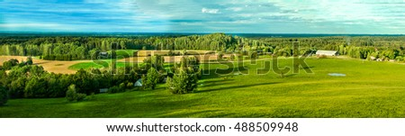 Beautiful Latvian countryside panorama of green field above the blue sky