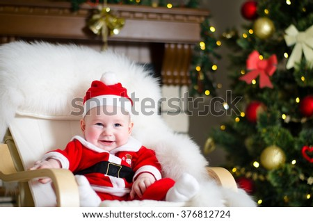 Beautiful laughing baby in a suit of Santa Claus sitting in a chair next to the fireplace and decorated Christmas tree on Christmas Eve night. The background. - stock photo