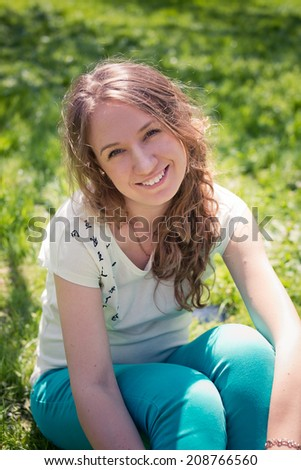 Beautiful laughing girl in green jeans sits on green grass.