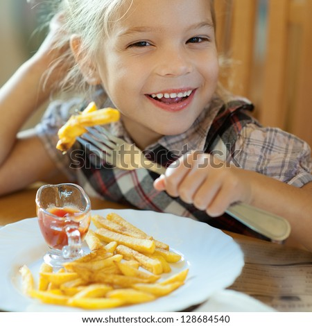 Beautiful laughing little girl sitting at table and eating French fries from your plate. - stock photo