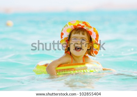 Beautiful  laughing little girl 3 years old dressed in yellow hat floats in the sea on inflatable wheel - stock photo
