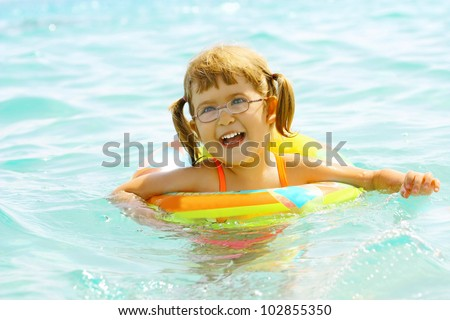 Beautiful laughing little girl 3 years old floats in the sea on inflatable wheel - stock photo