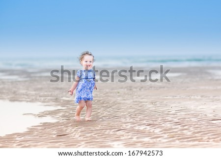 Beautiful laughing toddler girl with curly hair in a blue dress running at a tropical beach