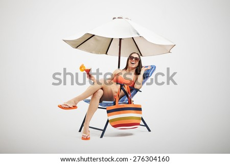 beautiful laughing woman in bikini and sunglasses relaxing on beach chair and holding cocktail under beach umbrella over light background - stock photo