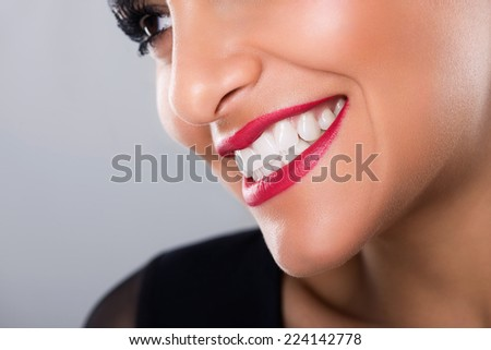 Beautiful laughing woman with red lips and white teeth, closeup, on grey background, studio shot - stock photo