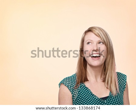 Beautiful laughing woman with space for advertising copy or text - stock photo