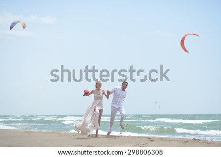 Beautiful laughing young wedding couple of man and woman in white jumping and running along ocean beach shore on windy weather sunny day with paraplanes on blue sky background, horizontal picture - stock photo