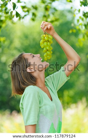 Beautiful laughing young woman eating grapes, against background of summer green park. - stock photo