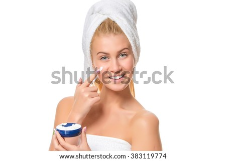 Beautiful laughing young woman with facial cream on her cheek - stock photo