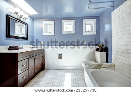Beautiful lavender bathroom with white wall trim . Vanity cabinet with drawers and mirror. White bath tub with tile wall trim - stock photo