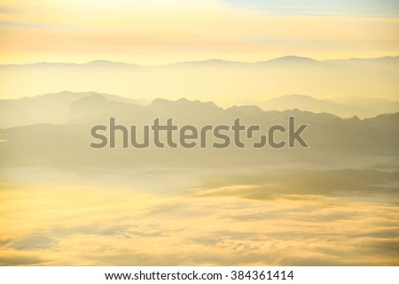 Beautiful layers of mountain range landscape with winter sky from top view in majestic sunrise and fog - stock photo