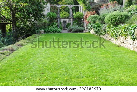 Beautiful Leafy Garden and Lush Green Lawn - stock photo