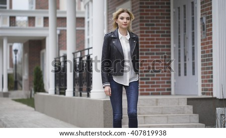 Beautiful leggy blonde confident gait walking down the street. Black leather jacket, brick houses - stock photo