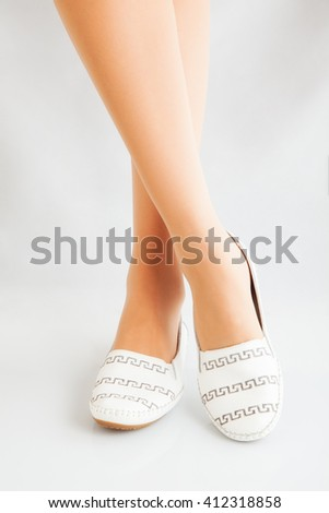 beautiful legs in a comfortable elegant shoes on a white background - stock photo