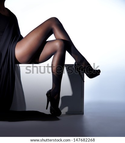 Beautiful legs in nice stockings over white background - stock photo