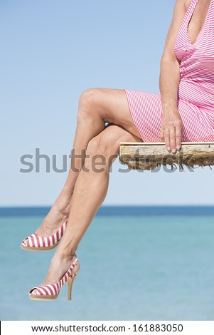 Beautiful legs of mature woman sitting in sexy pose on platform at the ocean, wearing summer dress and high heels, overlooking tropical sea, with horizon and blue sky as background and copy space. - stock photo