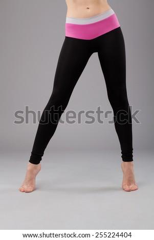 Beautiful legs of sporty woman in leggings - stock photo