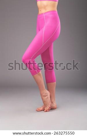 Beautiful legs of sporty woman in pink leggings - stock photo