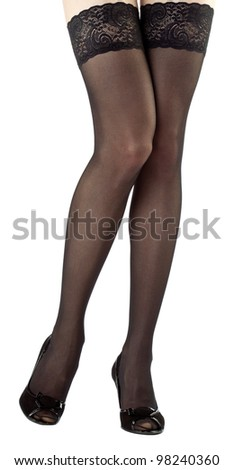 Beautiful legs of young woman wearing black stockings; isolated on white - stock photo