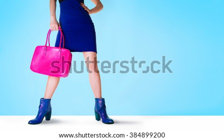 Beautiful legs woman with blue boots and pink bag. Isolated on blue with copy space. Fashion shopping image.  - stock photo