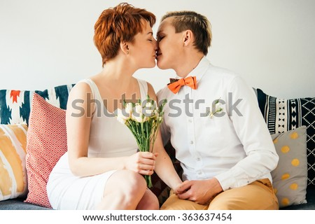 Beautiful lesbian couple kissing while celebrate their wedding. Gay marriage concept. - stock photo