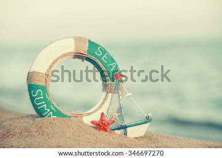 Beautiful life buoy in the sand with boat toy on unfocused sea background - stock photo