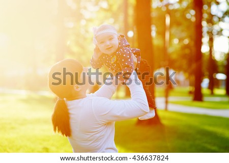 Beautiful lifestyle summer photo mother and baby girl walks in the park - stock photo