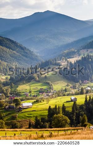 Beautiful light beam in morning with village on mountain valleys   - stock photo