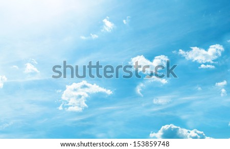 Beautiful light blue sky background with white sparse clouds and sun in autumn - stock photo