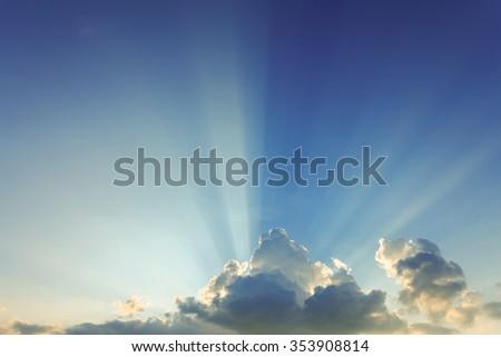 beautiful light of sunbeams, light rays on dramatic sunset sky background - stock photo