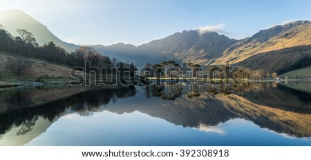 Beautiful light shining through mountains on a fresh spring sunny morning at Buttermere in the Lake District, UK.