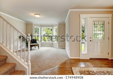 Beautiful light tones hallway with chair and palm open to entrance hall - stock photo