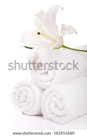 Beautiful lilly on towels rolls isolated on white  - stock photo