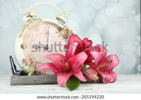 Beautiful lily with clock on wooden tray on bright background - stock photo
