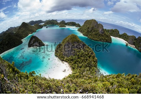 Beautiful limestone islands surround a gorgeous lagoon in Raja Ampat, Indonesia. This remote region, known as the heart of the Coral Triangle, is home to an amazing amount of marine biodiversity.