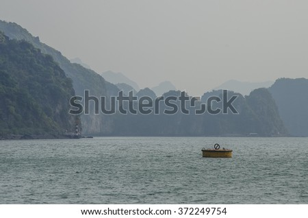 Beautiful limestone mountain scenery with yellow buoy at Ha Long Bay, North Vietnam. Cloudy winter weather - stock photo