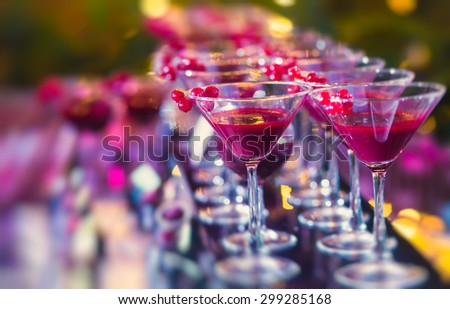 Beautiful line of different colored alcohol cocktails with mint on a open air party, tequila, martini, vodka, and others on decorated catering bouquet table on open air event, picture with tilt shift - stock photo